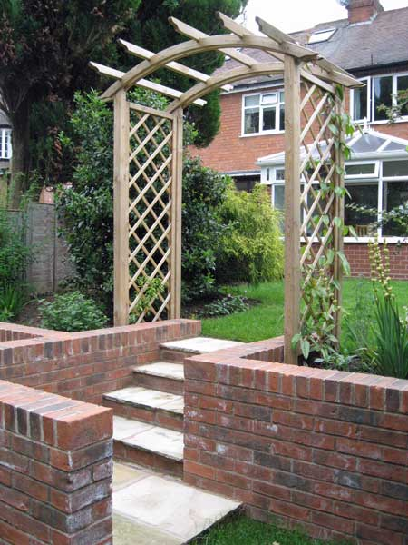 A steeply sloping garden on several levels, with a feature arch ...