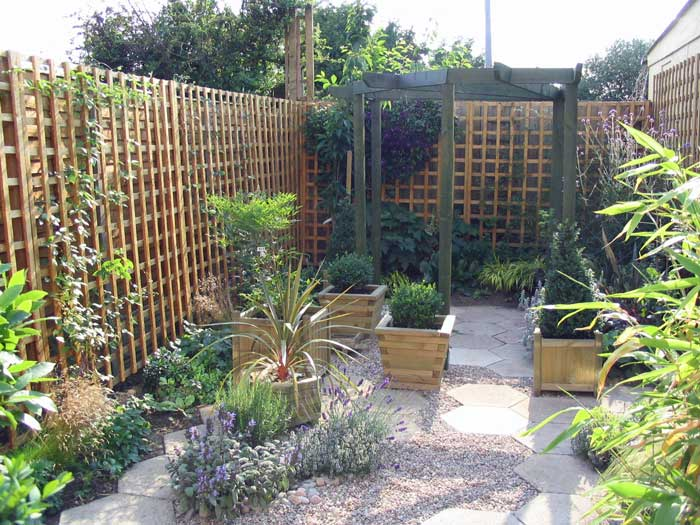 A small courtyard garden created around existing paving for Small garden courtyard designs